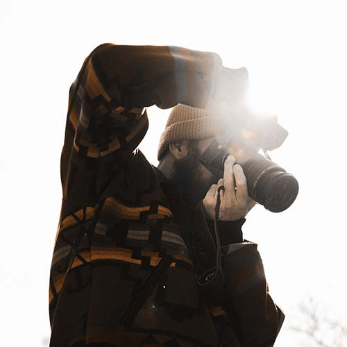 Image of Man taking photo with camera with light behind him_Size 500 x 500